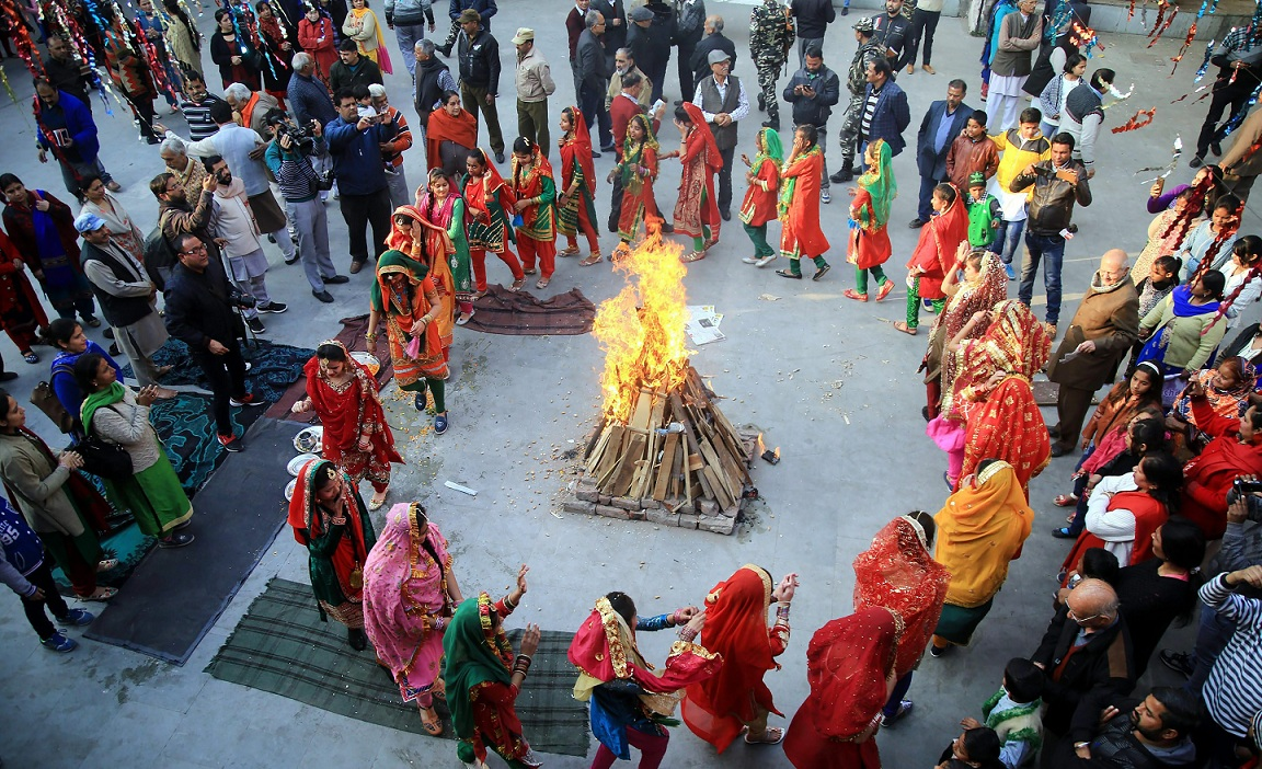 Girls dressed in their traditional attire dance around a bonfire as they celebrate Lohri in Jammu on Saturday. PTI