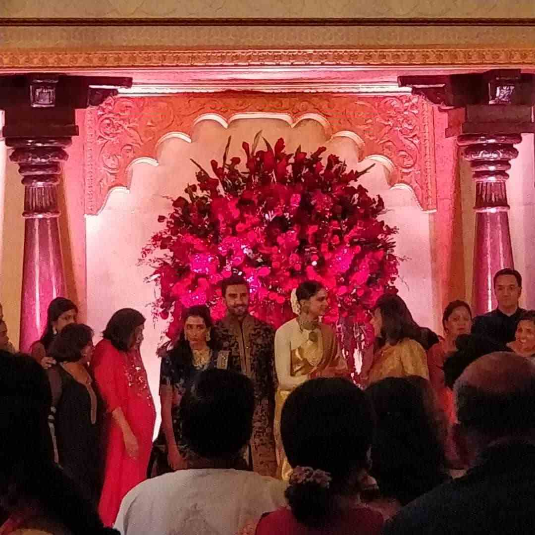 <p>Deepika Padukone and Ranveer Singh are seen greeting their guest. Don't miss the flowery decor in the backdrop. FYI: the power of pink is clearly evident at the reception as it is Deepika's most adored shade when it comes to flowers. Her Instagram proves the same. </p>