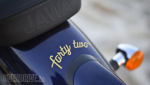 <p>The Forty-Two is named after the Hitchhiker&#39;s Guide to the Galaxy. In that book, the number is the answer to Life, Universe and Everything. In the real world, the Jawa Forty-Two is, more or less, a de-chromed version of the Jawa Jawa. It does have a flatter handlebar that sits lower which makes a slight difference in feel. The move from the nacelle to a regular fork-mounted headlamp also means that the single pod meter is mounted to the right, on a small spar that sits on top of the right fork leg. The Forty-Two is otherwise identical. Some very interesting colours are on the Jawa palettes, I really did like that dark blue shade on our test Forty-Two.</p>