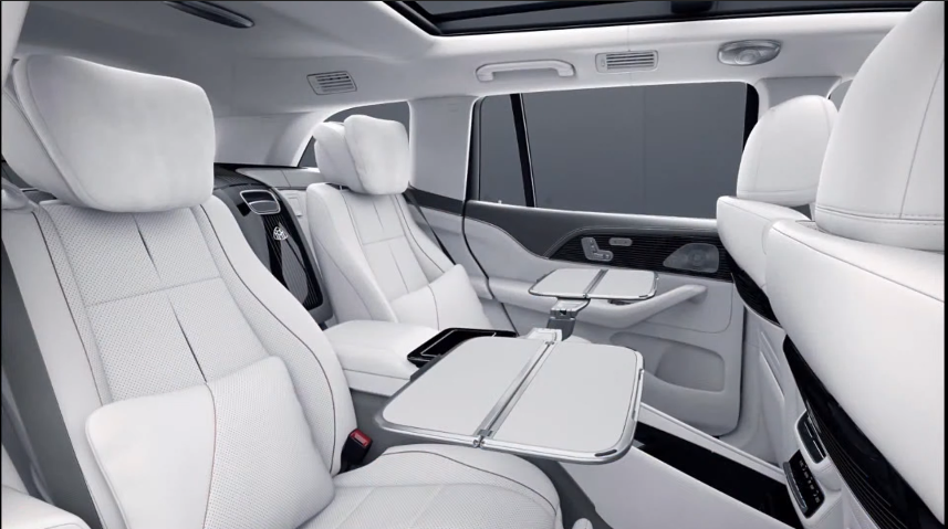 <p>There are stowable tray tables in the centre console of the rear seat, along with a rear entertainment package, heated/coolded seats and massaging functions</p>